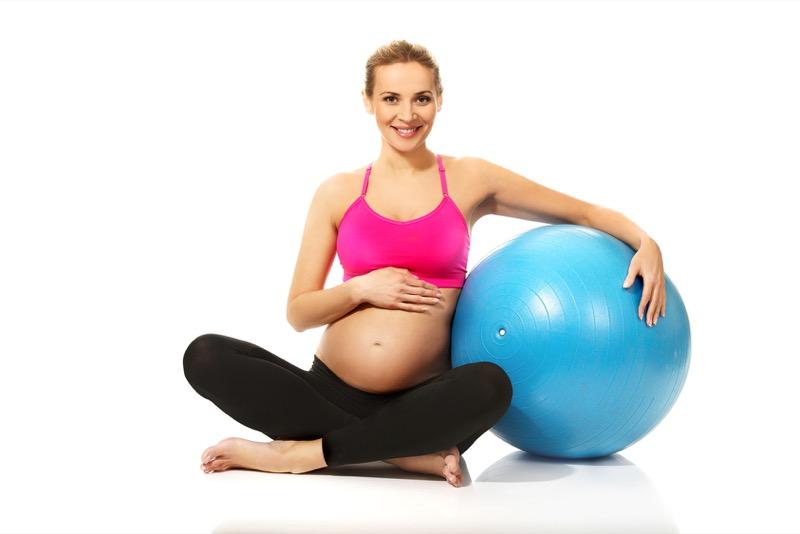 Pregnant woman sitting cross legged with gymnastic ball